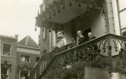 Op het bordes van het stadhuis op de Grote Markt staan H.M. Koningin Wilhelmina, haar echtgenoot Z.K.H. Prins Hendrik, burgemeester Gijsen en wethouder C. Houtman, tijdens           het koninklijk bezoek aan Schiedam in 1925.