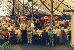 Tijdens de viering van het eeuwfeest van de St. Jacobuskerk in 1990. Zittend aan tafel links van de paal pastor C.A. Veltman die in gesprek is met dominee N.K. (Kees) Mos,           predikant van de Dorpskerk. Staande links achter hem bisschop Philippe Bär van Rotterdam. Rechts achter hem J.G. (Jan) van der Meer, voorzitter van het parochiebestuur.