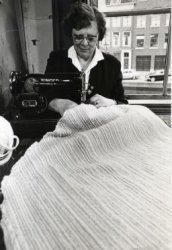 Mies van Rossum, handweefkledenkunstenares, aan de naaimachine in haar atelier Korte Haven 44.