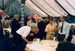 Tijdens de viering van het eeuwfeest van de St. Jacobuskerk in 1990 in een feesttent aan de Joppelaan. Schijvend Mgr.Ph.Bär, bisschop van het bisdom Rotterdam, die een           exemplaar van het boek over de Jacobuskerk signeert. Geheel rechts pastor Kees Veltman. Tweede van rechts Chriet Wilthaus.
