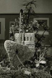 Bloemstuk, aangeboden aan koningin Juliana tijdens haar bezoek aan Schiedam in 1962. Het bloemstuk verbeeldt vier speciaal geslepen flessen met Schiedamse dranken. De           toezegging een volledige gymnastiek-uitrusting te verzorgen voor een door het koninklijk paar te stichten jeugdcentrum is hier gesymboliseerd door een draadfiguur van een           turner.