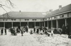De speelplaats met de zandbak op het binnenterrein van de Mariabewaarschool aan de Laan, omstreeks 1922. De naam van de school is verbonden met Maria Loopuijt. Zij schonk in           1843 het gebouw in de Nieuwstraat 22 waarin de school van 1843 tot 1920 gevestigd was.