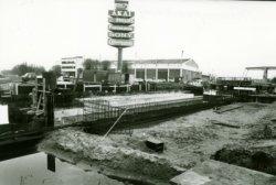 De in aanbouw zijnde Delflandburg ter vervanging van de in 1951 geplaatste door werf Gusto, afdeling Bruggenbouw gebouwde Hulpbrug (rechts) gezien in de richting van de           Nieuwpoortweg. Op de Nieuwpoortweg staat rechts het pand van Radio Modern.