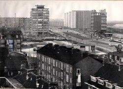 Gezicht vanaf een flat aan de Dieselstraat, gezicht op de Horvathweg, Plein 1940-1945 en de Burgemeester van Haarenlaan. Rechts de NS-flat met Station Schiedam, daarachter           de vier 12-hoogflats respectievelijk aan de 's-Gravenlandseweg, de Louis Raemaekersstraat en de Johan Braakensiekstraat. Linksmidden op de achtergrond, de kantoorflat op het           Stationsplein.