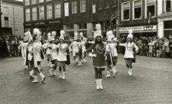 Majorettes tijdens de 21ste Koningin Wilhelminamars op de Grote Markt. Daarachter de winkels van Van Dijk radio en televisie (nr.17), Plate & Co, woninginrichting en           toonkamers (nr. 19) en de optiek van Ferd. Overdijk (nr. 23).