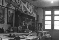 Het interieur van het atelier van de gebroeders Henderickx aan de Oude Sluis. Centraal een kast met verschillende stukken glas.
