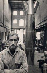 Een kunstenaar in zijn atelier met op de achtergrond zijn project.