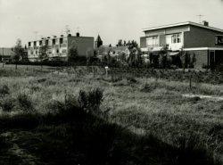 De achterzijde van huizen aan de Kerklaan. De maisonnette woningen staan op de Meeuwensingel. Op de voorgrond de put. die in november 1964 is ontstaan bij de opgraving van           een Keltische boerderij. In verband met dreigende verzakkingen is de put weer haastig dichtgegooid. Op de achtergrond is de toren van de Hervormde kerk zichtbaar.