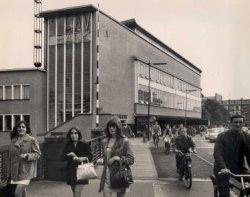 Gezicht vanaf de Koemarkt in de richting van de Gerrit Verboonstraat met links het kantoorgebouw van de HAV-Bank (Hollandse Algemeene Verzekerings Bank) met winkels eronder,           gebouwd in 1933-1935 naar ontwerp van de Hilversumse architect W.M. Dudok in een Zakelijk Expressionis-tische bouwstijl.