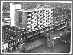 De Broersvest, gezien vanaf de flat Singelwijck. Links is nog net een stukje van het dan nog verdiepte deel (de put) van de Broersvest te zien met een café en een slagerij.           Daarnaast nieuwbouw met rijwielhandel I.D.W. en dan de hoge flat, bekend als de 'flat van Vlug'. Bakker M.J. Vlug liet de flat bouwen en woonde er. Daarnaast lagere nieuwbouw met '           Kledingmagazijn Bervoets' op de hoek met het Herenpad.
