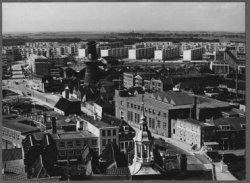 Een overzicht vanaf de toren van de Grote of St Janskerk in de richting van de Vijgensteeg en het Spinhuispad. Op de achtergrond woonflats in de wijk Nieuwland links en           rechts van de Parkweg. Op de voorgrond het torentje van het Stadhuis op de Grote Markt.