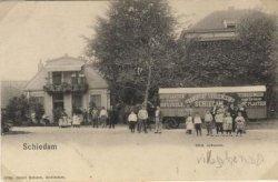 Het Hoofdplein gezien van het Hoofdplein in de richting van de villa Johanna op hetzelfde plein. De verhuiswagen van de Transport Vereeniging Schiedam met paard is kennelijk           voor de reclame neergezet. Opm. Zie ook