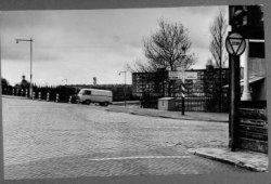 De Vlaardingerdijk, gezien vanuit de Vlaardingerstraat in de richting van de bejaardenflats in Nieuwland. Rechts op de hoek nog juist zicht een klein stukje van het           restaurant van H.C.R. Beijersbergen. Rechts om de hoek, de Vellevest en iets verderop de Vellevestsingel. Geheel links de koepel van de kapel op de R.K. begraafplaats.