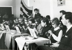 Bij de viering van het 10-jarig bestaan van het Sint Liduinalyceum, sinds kort geheten Spieringshoeklyceum, wordt o.a. een officiële bijeenkomst gehouden in de           gymnastiekzaal van de school. Tijdens deze bijeenkomst speelt het schoolorkest een intermezzo.