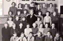 Een klassenfoto van de Klaas de Vriesschool aan de Zwartewaalsestraat met in het midden meester A.Hukshoorn. Naamlijst en nummering van personen in de map aan de balie in de           studiezaal
