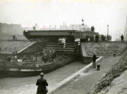 Het transport met het brugdek van de nieuwe Oranjebrug passeert hier de buitensluis. Het brugdek is gemaakt bij de N.V.Swarttouw te Schiedam.