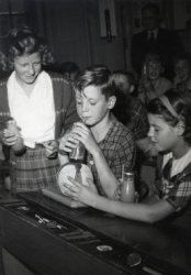 Drinken van melk in de schoolklas in het kader van schoolmelkvoorziening die in 1937 in Rotterdam met een proef begon. Eind jaren vijftig ontvingen bijna alle Nederlandse           lagere scholen schoolmelk. In de jaren 70 van de 20e eeuw dronken ca. 700.000 kinderen de melk op school. Nu, 2012, zijn het er nog ongeveer 120.000. Het is onbekend op welke school de foto           is gemaakt.