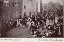 De Gerrit Verboonstraat ongeveer gezien vanaf de hoek met de Tuinlaan in de richting van de (oude) Koemarktbrug en Koemarkt. De optocht is ter gelegenheid van de           Onafhankelijkheidsfeesten (sedert Napoleon). In het witte pand, op de hoek met de Lange haven, is nu café De Unie gevestigd.