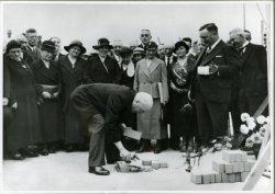 De eerstesteenlegging van het St. Jacobs Gasthuis aan de Burgemeester Knappertlaan door burgemeester Hendrik Stulemeyer op 20 september 1933. Architect Piet Sanders op de           voor-grond , kijkt lachend toe. De 4e dame van links is directrice M. Kros, de 6e van links (met lichte kleding) is mevrouw E. Koeten-Ooms, regentes. Achter haar Ir. C.E. Alexander, adjunct           directeur Gemeentewerken.