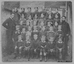 Een schoolklas van de 1e Openbare Armenschool (later genoemd School C), Lange Nieuwstraat achter het Blaauwhuis. Op het bord boven de groep staat geschreven: School           Plantage. De foto is vermoedelijk omstreeks 1890 gemaakt.