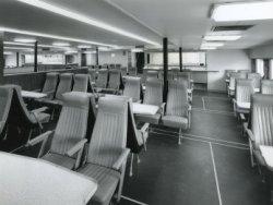 Een overzicht van een deel van het passagiersverblijf van de veerboot 'Free Enterprise III' (Co.538), die door de opdrachtgever 'Townsend European Ferries' werd ingezet voor           de overtocht Dover-Calais. De inrichting was sober met 'treinsgewijs' opgestelde leunstoelen. Aan het eind zien we de twee geopende buffetten voor het aanschaffen van een lichte maaltijd           en/of versnaperingen tijdens de overtocht. Het schip kon 1.114 passagiers herbergen 221 auto's en had een 76 koppige bemanning.
