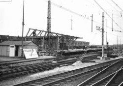 Het goederenemplacement van de Nederlandse Spoorwegen langs de Parallelweg, gezien vanaf het perron noordzijde. De (sloop)werkzaamheden i.v.m. de aanstaande bouw van een           nieuw NS-station zijn begonnen. Op de achtergrond links: panden aan de Parallelweg.