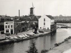 Pakhuizen aan de Noordvest gezien vanaf een pand aan het Schuttersveld in de richting van molen de Drie Koornbloemen. Rechts woningen aan de Vlaardingerdijk. Het hoge witte           pand (deels in de stellingen) is de voormalige stoommolen Den Draak.