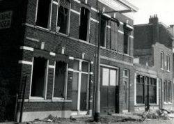 Sloop van de Overschiesestraat oostzijde tussen Stationsplein en Overschiesedwarsstraat. Rechts de pui van café Ploos van Amstel. Het bovengedeelte van dat pand is reeds           verdwenen. Het café was al in februari 1960 of eerder dichtgetimmerd.