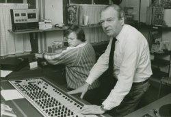 W. Groeneweg aan het bedieningspaneel in de studio van Radio Schiedam. Links Pim Scheenloop.
