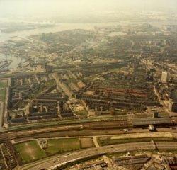 Luchtfoto van het oosten van Schiedam. Op de voorgrond rijksweg A20 en de spoorlijn Rotterdam-Hoek van Holland met rechts het NS-station Schiedam. Op de achtergrond de           Nieuwe Maas.