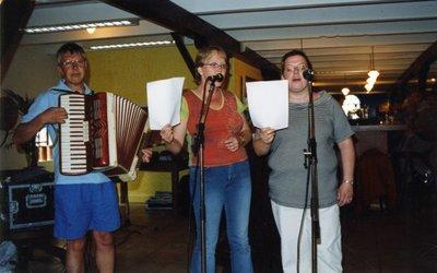 Sg. Spieringshoek houdt op 30 juni 2004 de jaarlijkse personeelsdag. Deze keer in en om een boerderij aan de Zuidweg tussen Vlaardingen en Maassluis. Er wordt o.a. afscheid           genomen van natuurkundedocent H.J.J. Noordam. Collega's F.C. Thier (mer accordeon), M.J.de Ridder-de Groote en M. Bontenbal zingen hem toe.