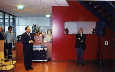 In de mediatheekruimte van sg. Spieringshoek spreekt de komende rector, L.J. Timmermans, het personeel toe op 6 januari 2003. Rechts rector H.J.N. Schoenmakers. Links docent           K.van Asch en technisch onderwijsassistent A.I. Voskuilen.