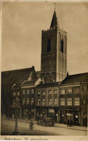 De Grote Markt met op de achtergrond de toren van de Grote of St. Janskerk staande in de Nieuwstraat. De nieuwe torentrans is bijna gereed (vaag is nog een takel te zien)           van de ombouw van hekwerk naar stenen trans. Deze restauratie duurde van 1932 tot 1934 (Volgens Max Verkade vermeldt drs G. van de Feijst die datums onjuist). In de panden op de Grote Markt           zaten/ woonden v.l.n.r. 1e pand: Rijwielhandel Ter Braak; 2e pand: beneden Bakkerij Gerritsen vh. Chocolaterie Nolet en boven de dames Nederpelt; 3e pand: Grammofoonplatenwinkel (later           Verkuijl) 4e pand; Schoenwinkel Beumers en banketwinkel Dubbeld (later Bartels).