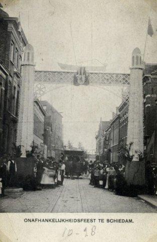 Ereboog naar aanleiding van 100 jaar Nederlandse Onafhankelijkheid in met de daarbij horende feesten. Hier in de Hoofdstraat in 1913, ter hoogte van de (voormalige)           Fabrieksstraat. Alles gezien in de richting van het Hoofd. De paardentram is op weg naar het station.
