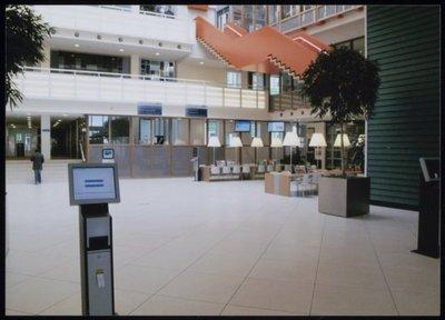 Zaandam. Stadhuisplein. Publiekshal stadhuis Zaanstad. De publiekshal is ruim en hoog. Majestueus, maar toch intiem dankzij de details, de leestafels en de wijze waarop de           balies gepositioneerd zijn. Doordat de kap op het achterste deel van de publiekshal van glas is krijgt het daglicht alle kans om vanaf grote hoogte binnen te vallen. De oranje trap valt op           en leidt naar de tweede verdieping en de foyer. Vandaar loopt een brede balustrade naar de raadszaal. Op welk niveau je je ook bevindt in de hal, overal kun je contact maken met de           tegenoverliggende verdiepingen en heb je vrij uitzicht op de begane grond.