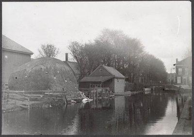 Zaandam. Papenpad. Gezicht op oude Papenpadbrug. Papenpadsloot en sluis lopend van de Zaan naar het Westzijderveld. De sloot verbindt de Zaan met de Gouw. De sluis behoort           tot de oudste nog bestaande sluizen in de Zaanstreek. De eerste vermeldingen van sloot, sluis en pad stammen uit de eerste helft van de 17e eeuw. Het pad heette aanvankelijk het Jacob           Dirckxpad. Deze naam werd in de 18e eeuw gewijzigd, toen een katholieke kerk aan het pad was gebouwd. Het padreglement is van 1754. Wanneer de sluis voor het eerst is aangelegd is niet           bekend, wel dat deze in 1681 in zodanige staat verkeerde dat vernieuwing geboden was. In 1722 is de sluis overgedragen aan Westzaandam, hetgeen er op kan wijzen dat hij voor de Banne van           Westzaanden van weinig belang was.