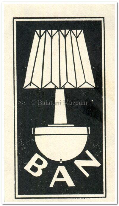 B A N betűk asztali lámpa alatt.