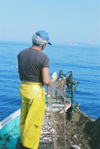 Fonds Henri-Paul Brémondy : Un pêcheur vu de dos avec un filet de pêche sur un bateau - Photographie en lien avec le corpus sonore La pêche traditionnelle varoise dans les années 1970