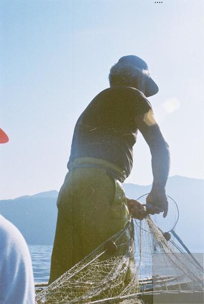 Fonds Henri-Paul Brémondy : Un pêcheur avec un filet de pêche dans un bateau - Photographie en lien avec le corpus sonore La pêche traditionnelle varoise dans les années 1970