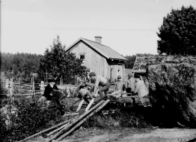 Träbearbetning (snickeri), en man som sågar, en man med dragspel, tre pojkar. Bostadshus i bakgrunden.