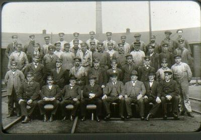 SJ:s personal vid lokstallarna före omläggningen till elektrisk drift. I början av 1920-talet. Uppifrån och från vänster: Rad 1: 1. eldare K. Skytt, 2. maskinskötare. K. Johansson, 3. v.o.st.k. Lindstedt, 4. v.o.st.k. Augustsson, 5. lokrep.K. Wallin, 6. lokrep, nu i  Göteborg, 7. v.o. st.k. nu i Nässjö, 8. e.eld.Andersson, 9. svarv. Holmer, nu i Göteborg, 10. pannsköt. Sv. Kroon,  11. e.v.o.st.k. Jansson, 12. v.och st.k. Jansson. Rad 2: 1. v.o.st.k .Fransson, 2. lokeld. A.Bergström 3. lokrep.Lundahl, 4. lokrep. Frigell, 5. v.o.st.k. Engström, 6. v.o.st.k. S. Bergqvist, 7. lokrep. Lundin, 8.lokrep. Jönsson, nu i Elmhult, 9.v.o.st.k. K. Öberg 10. lokrep. Jönsson, nu i Nässjö, 11. eld. Ekengren, 12. lokrep. Ljungman, 13. m.o.pannsköt. Eriksson, 15. v.o.st.k.  Daag. Rad 3: 1.v.o.st.k. Sjösten, 2.Lokeld. A.Nilsson, 3. lokf. A.Th. Brandt, 4.lokrep. A. Ruud, 5.lokrep. Blomén, 6. lokeld. Olsson, 7. lokeld. Nordenstam, 8.v.o.st.k. Sjöblom, 9. lokrep. H.Bengtsson, 10. lokrep. Svensso