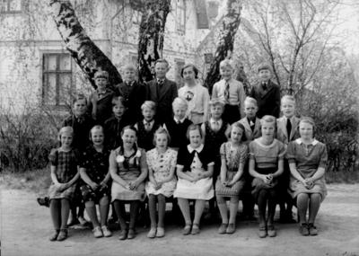 Rynninge skola, 8 flickor, 12 pojkar och lärarinna fru Eva Dahlen på skolgården. Skolbyggnad i bakgrunden.