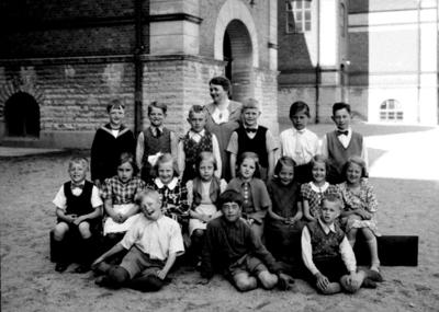Olaus Petriskolan, 17 skolbarn med lärarinna fröken Elisabeth Grahn på skolgården. Skolbyggnad i bakgrunden. Sal 4.