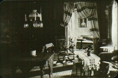 Interiör, Warenbergs hem (Tyskatomten). Förmaken sett från salen. Taget 1902 före auktionen. Fotografen har stått framför tamburdörren. På tamburen var en balkong. Drottningtavlan hänger på ytterväggen till Ekmans gränd. Det vita broderiet bakom gungstolen  hör till en stor duk som täcker taffelpianot. Detta forslades på landsväg från Stockholm. Otto Warenberg var en mycket god vissångare. Otto Warenberg född 1839, död 1902. Helga Warenberg född 1843, död 1899. Arvinge:Karl Alfred Warenberg, f. 24/7 1878.