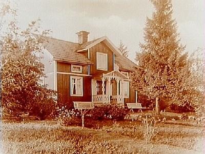 En och en halvvånings bostadshus med frontespis och veranda i snickarglädje. Adamsson (genom konsulent Flodkvist)