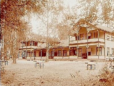 Envånings bostadshus med tvåvånings flyglar, veranda längs hela framsidan av huset, balkonger på flyglarna.