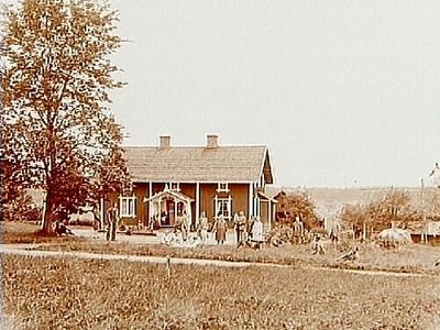 En och en halvvånings bostadshus med veranda och förstuga, 19 personer framför stugan. Gustaf Larsson