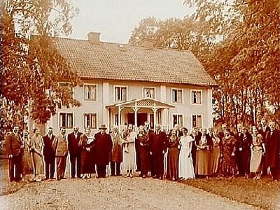 Tvvånings bostadshus med veranda i snickarglädje, 28 personer framför huset. Direktör Edstams 60 årsdag.