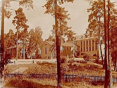Kyrkskolan i Danderyd till höger på bilden och Ålderdomshemmet till vänster. (Nr: 245.) På 1960-talet var det mellanstadieskola. Kyrkan ligger nära, på andra sidan den sedan gammalt stora vägen norrut, Norrtäljevägen/E18. Byggnaden till vänster var på 1960-talet kontor och rektorsexpedition. I källarplanet låg träslöjden. Syslöjden höll till på översta våningen i skolbyggnaden.