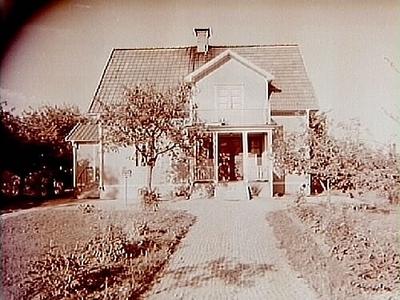 Envånings villa med inredd vind, frontespis, balkong, veranda och förstuga. En man och en kvinna till vänster om villan. Erik Larsson